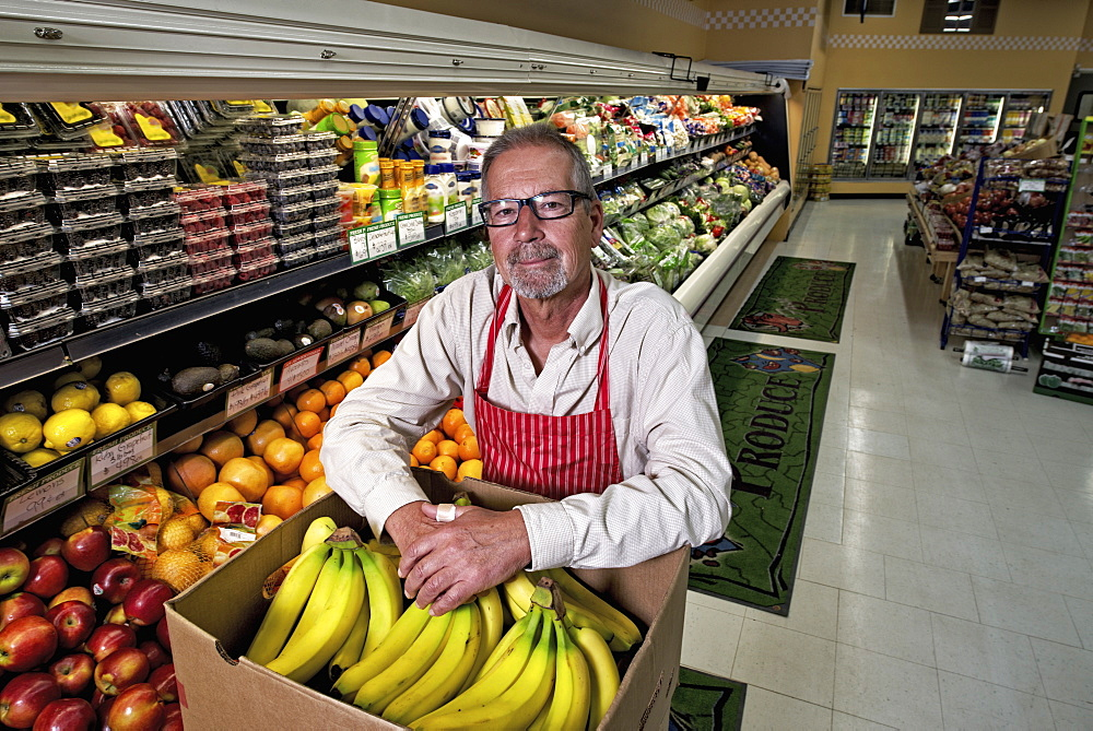 A man standing in a grocery shop beside a display of fresh fruits and vegetables.