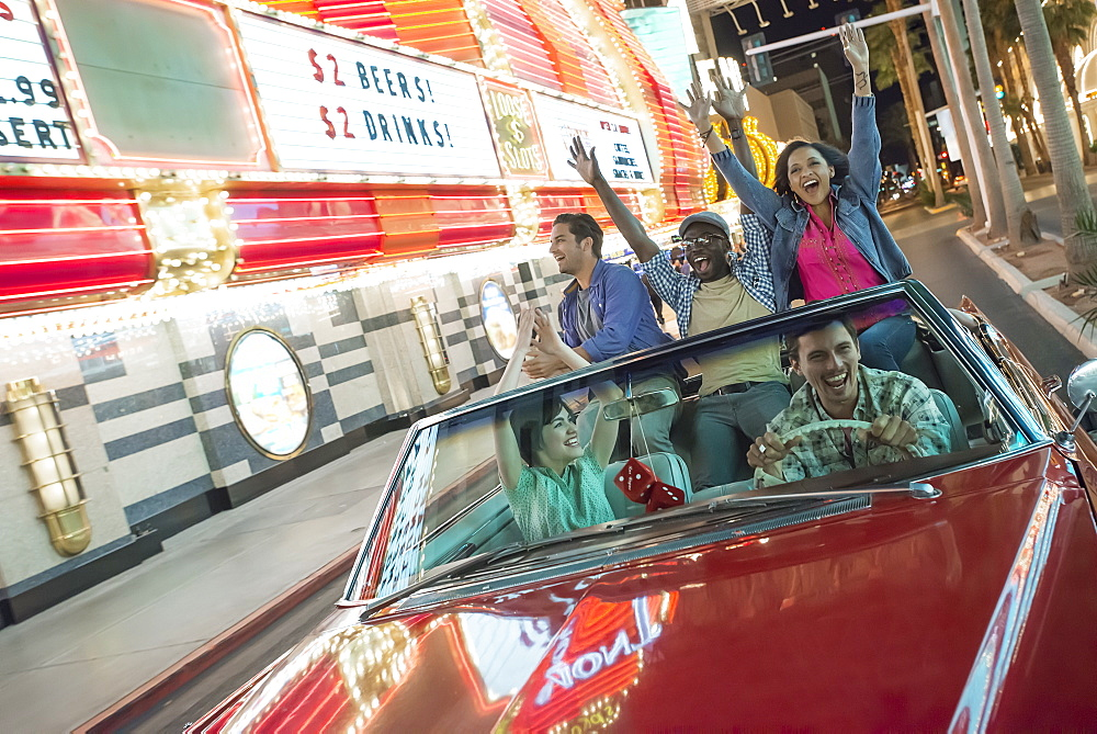 A group of friends in a red open top convertible classic car celebrating with waving arms as they drive through a city lit with neon signs, United States of America