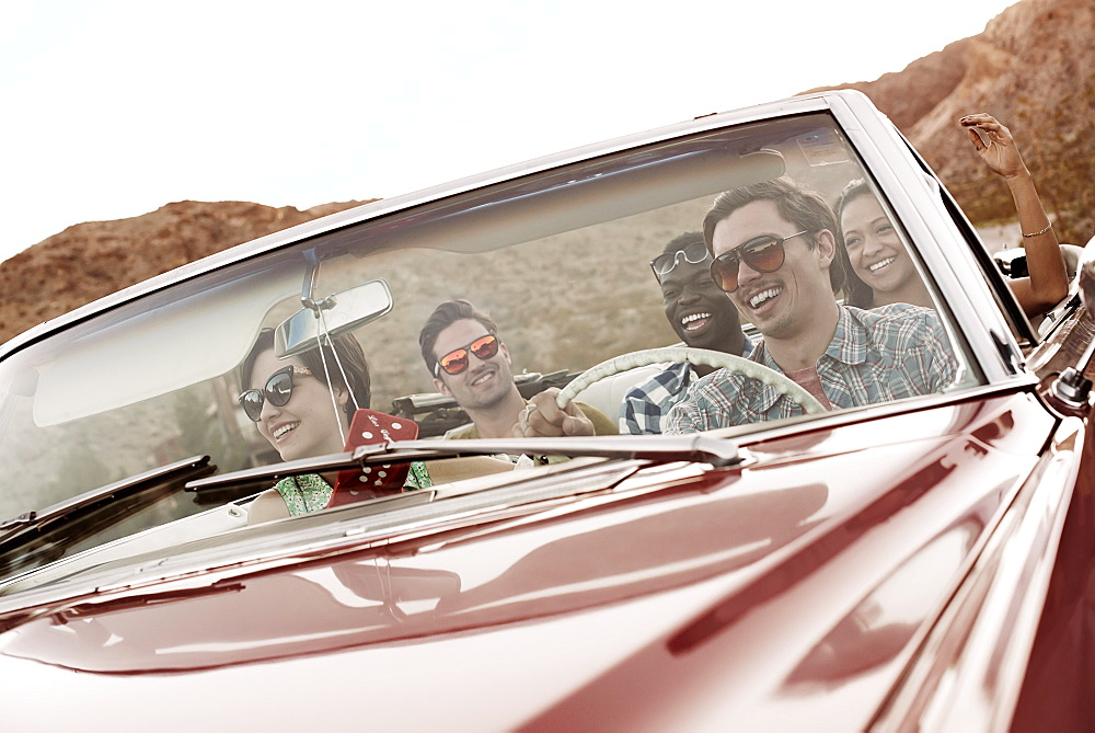 A group of friends in a red open top convertible classic car on a road trip, United States of America - 1174-4012