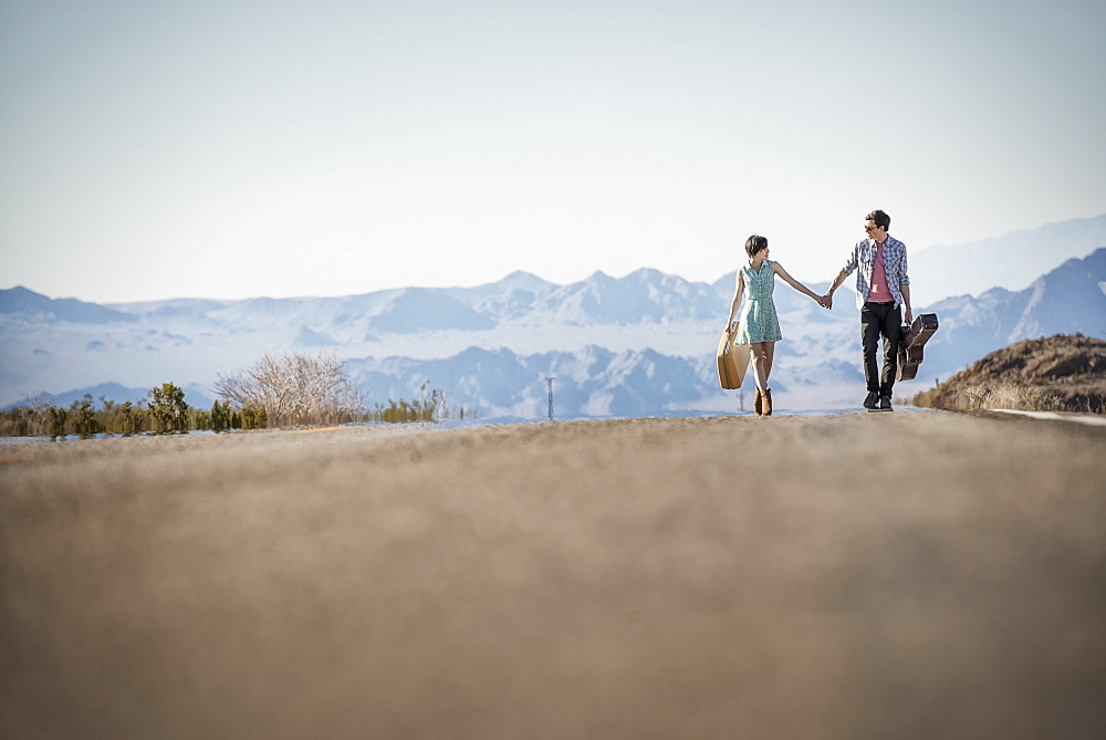 A young couple, man and woman walking hand in hand on a tarmac road in the desert carrying cases, United States of America