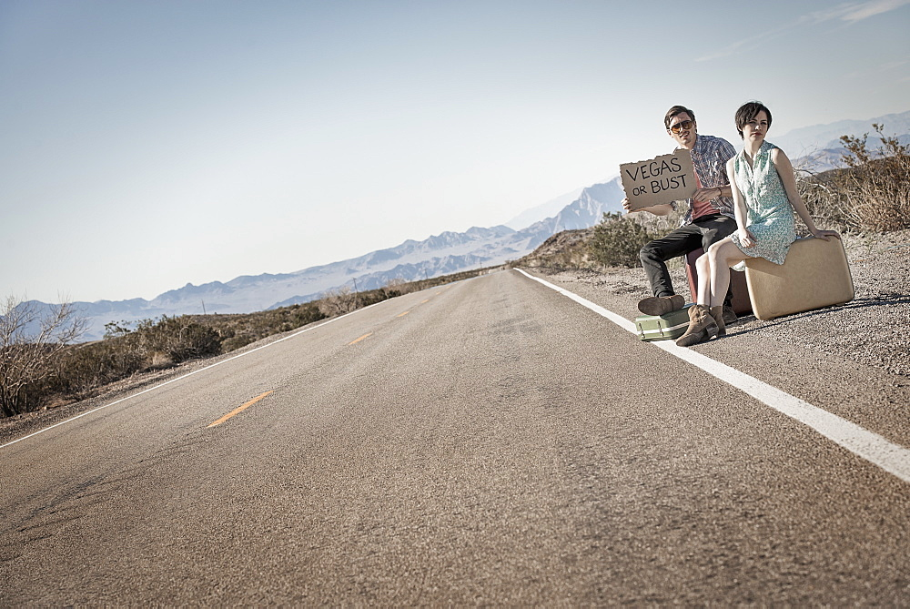 A young couple, man and woman, on a tarmac road in the desert hitchhiking, with a sign saying Vegas or Bust, United States of America