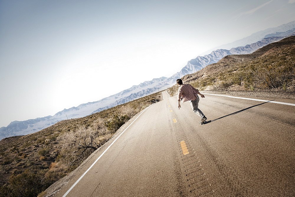 A young man riding down a tarmac road in the desert on a skateboard, United States of America