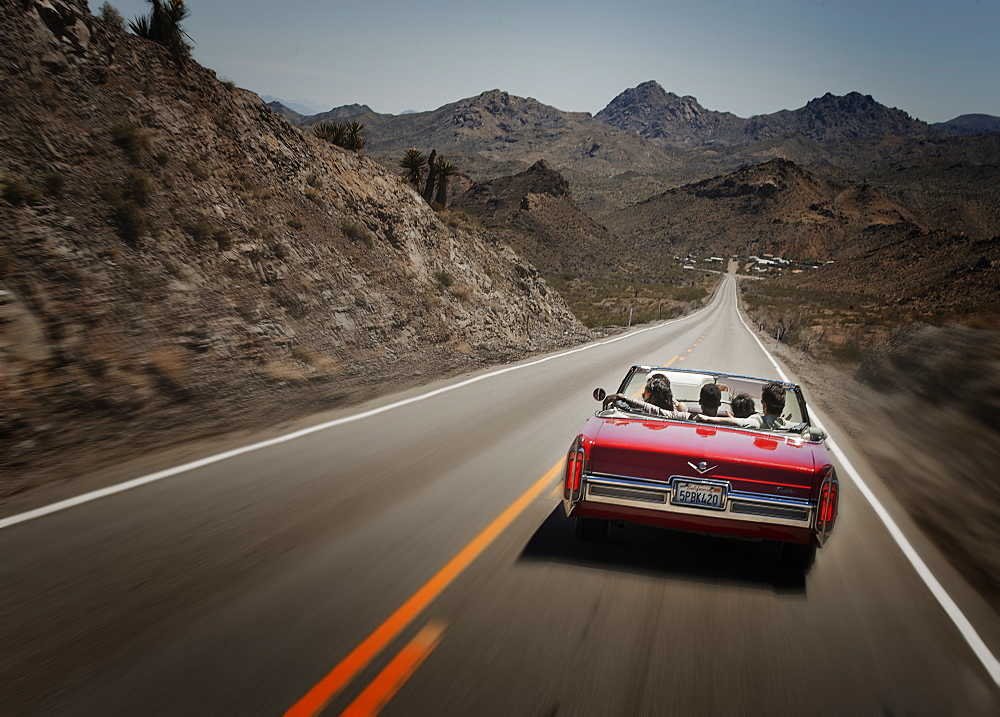 A red convertible car with five young people on a road trip. The open road, United States of America
