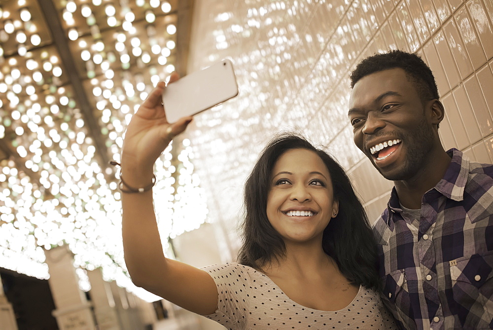 A man and woman in a brightly lit space, a casino entrance, taking a selfy with a smart phone, United States of America