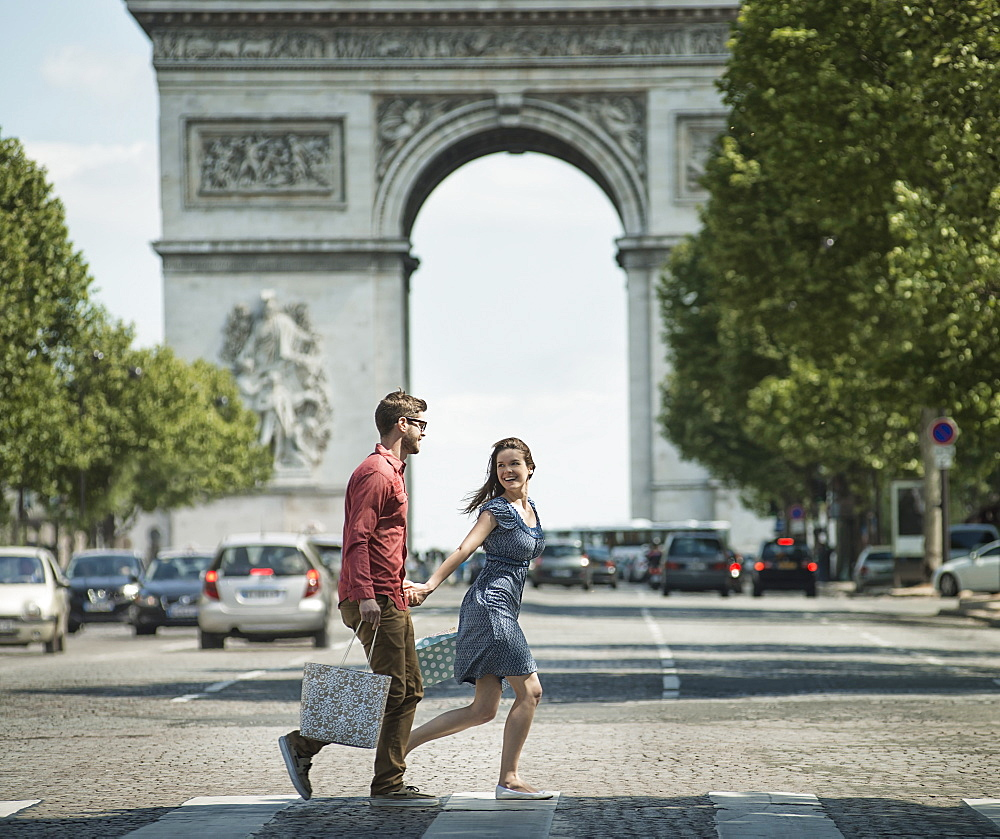A couple hand in hand carrying shopping bags and crossing the road by a historic monument in the heart of a European city, France