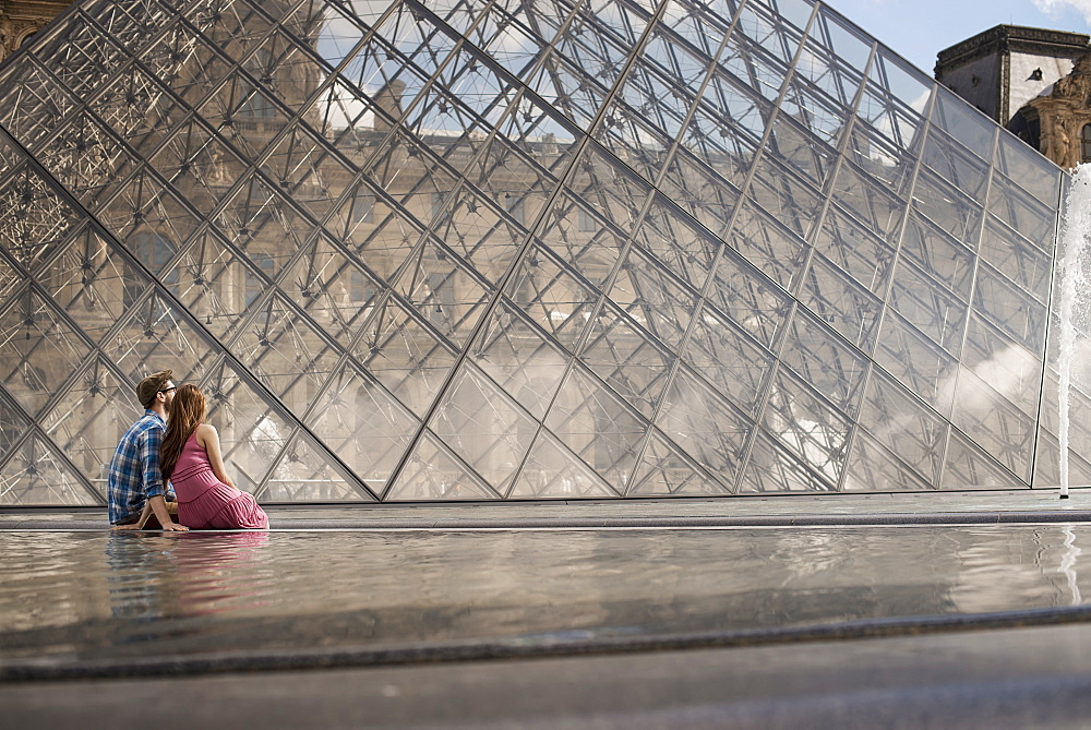 A couple in the courtyard of the Louvre museum, by the large glass pyramid. Fountains and water, France