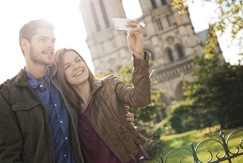 Two people, a couple standing close together taking a selfy outside the historic Notre Dame cathedral in Paris, France
