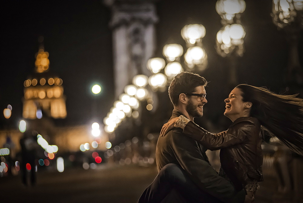 A couple close together facing each other, embracing in a city at night, France