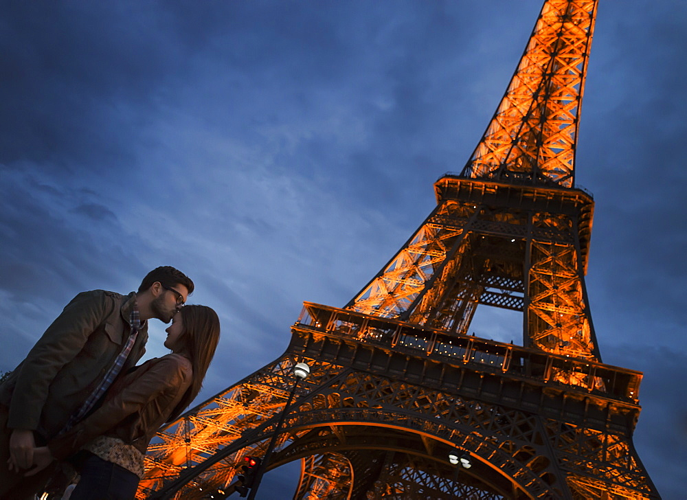 A couple standing under the lee of the Eiffel Tower at night in the Champs de Mars in Paris, France