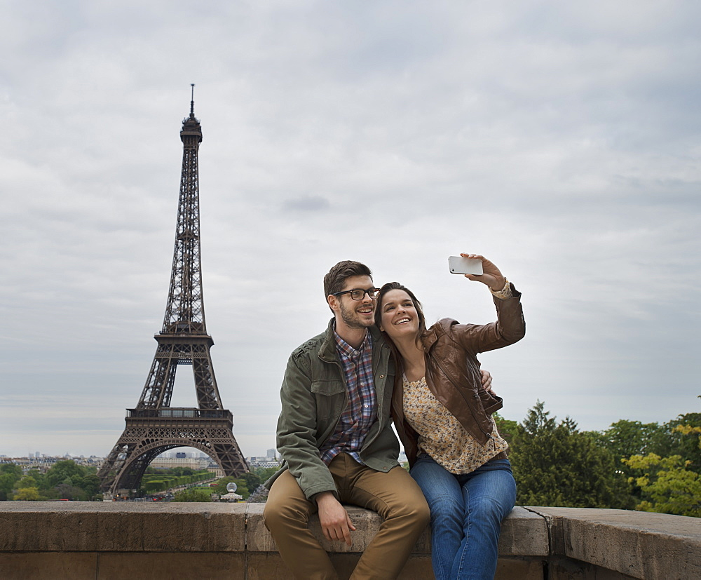 A couple seated side by side taking a selfy with the Eiffel Tower in the background, France