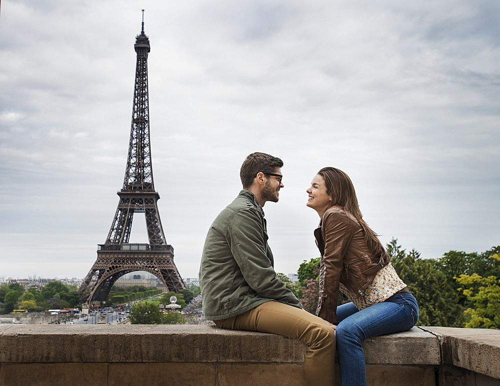 A couple seated facing each other on a wall in the city of Paris with the Eiffel Tower in the background, France