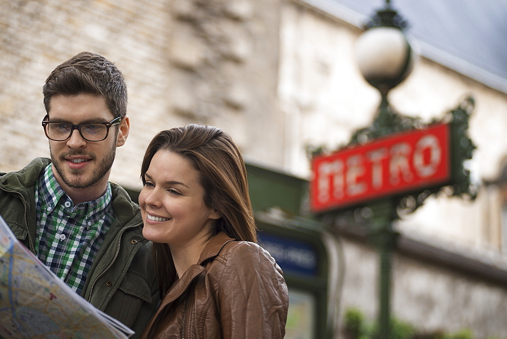 A couple consulting a map on a city street, under a classic Art Deco Metro sign, France