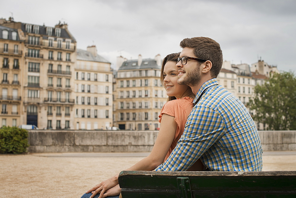 A couple, man and woman sitting close together on a bench by the River Seine, France