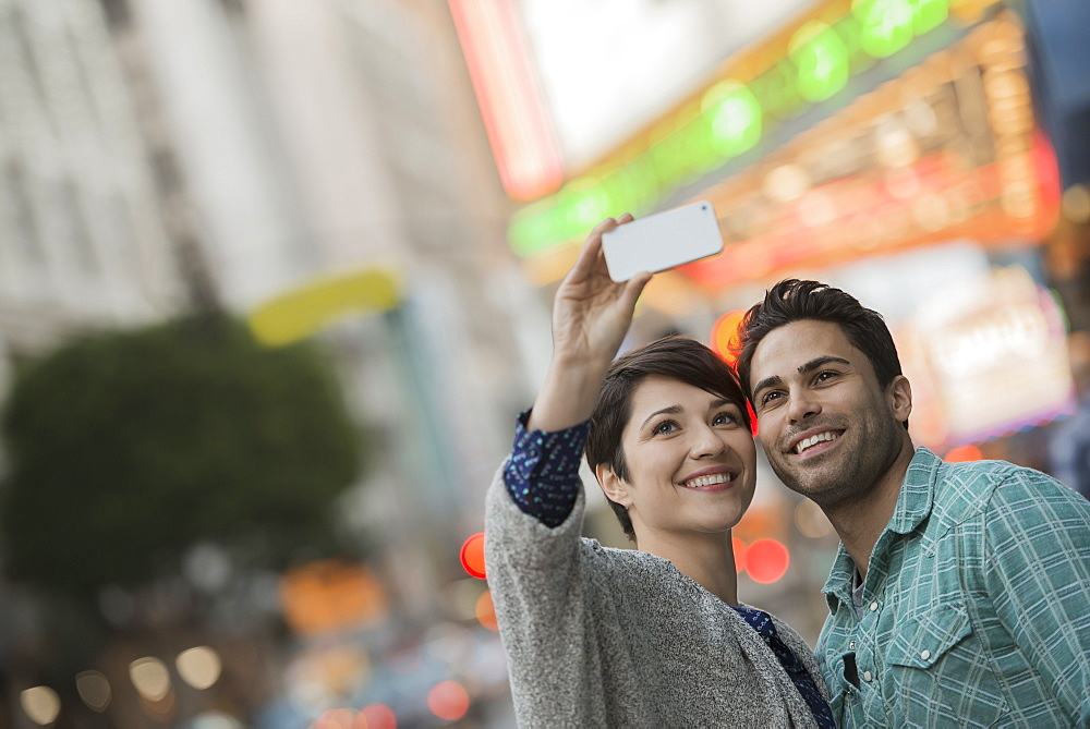 A couple, man and woman on a city street taking a selfy with a smart phone, United States of America