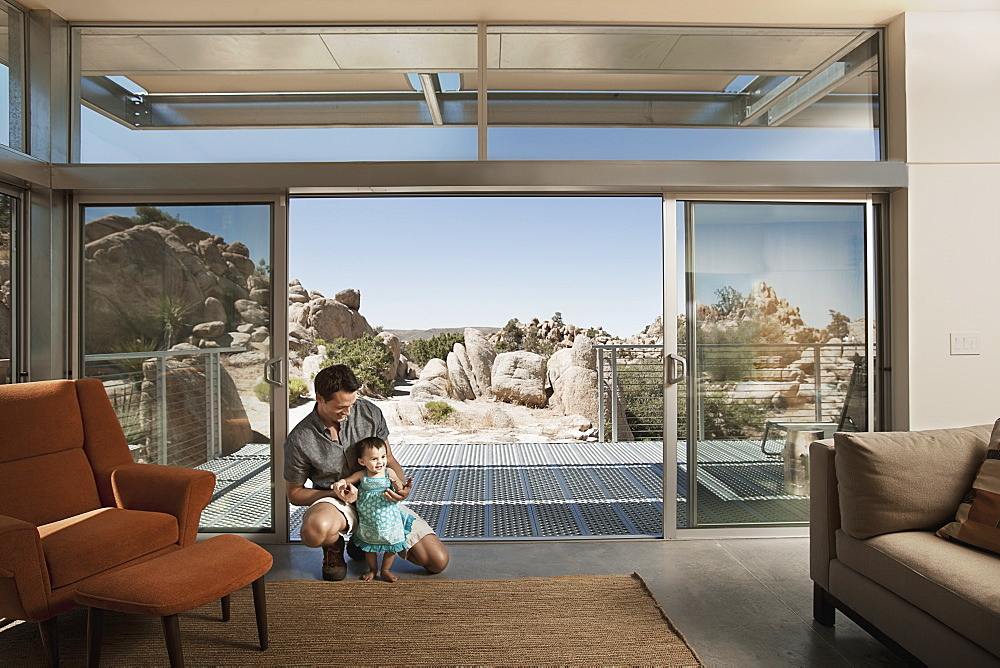 A man and a young child in an ecohouse, a home with large glass walls and view out over the rocky landscape, United States of America