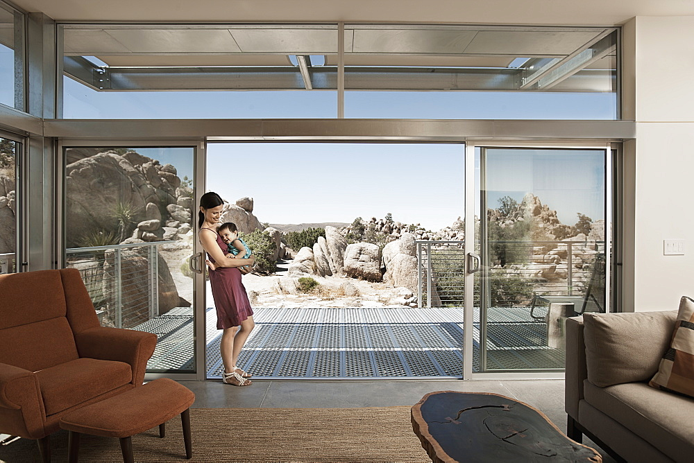 A woman and a young child in the living space of an eco house in the desert, United States of America