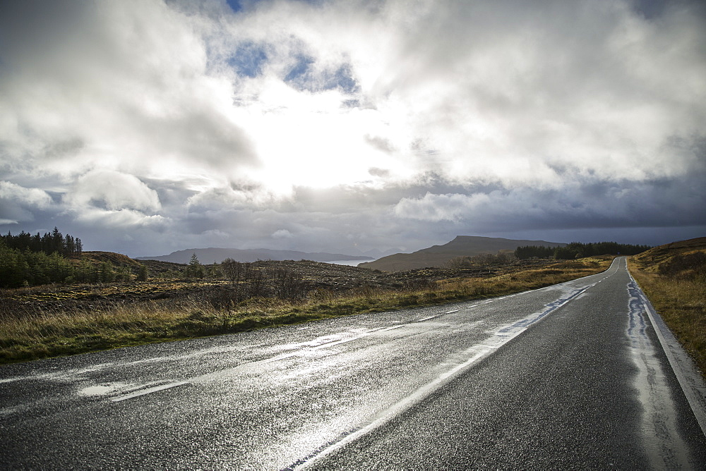 An empty two lane road through a deserted landscape, reaching into the distance. Low cloud in the sky, Scotland, United Kingdom