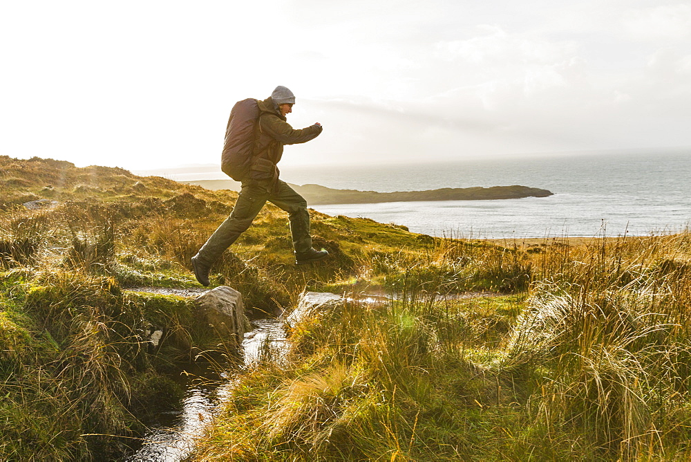 A man with a rucksack and winter clothing leaping across a small stream in an open exposed landscape, Scotland, United Kingdom