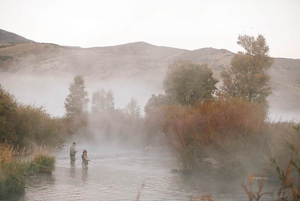 A couple, a man and woman standing in mid stream flyfishing in a river.