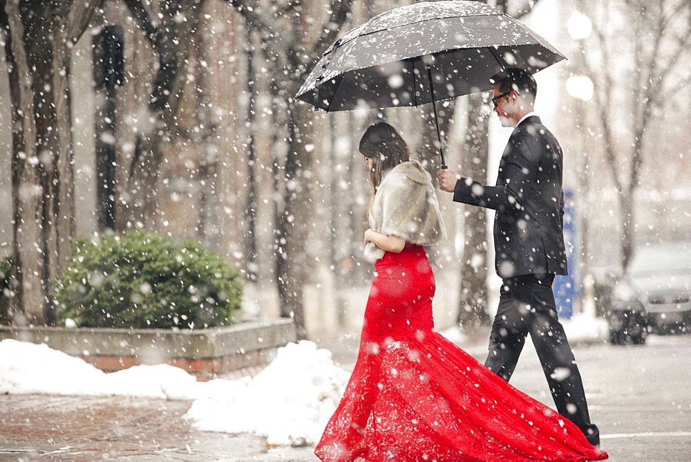 A woman in a long red evening dress with fishtail skirt wearing a fur stole, and a man in a suit, walking through snow in the city.