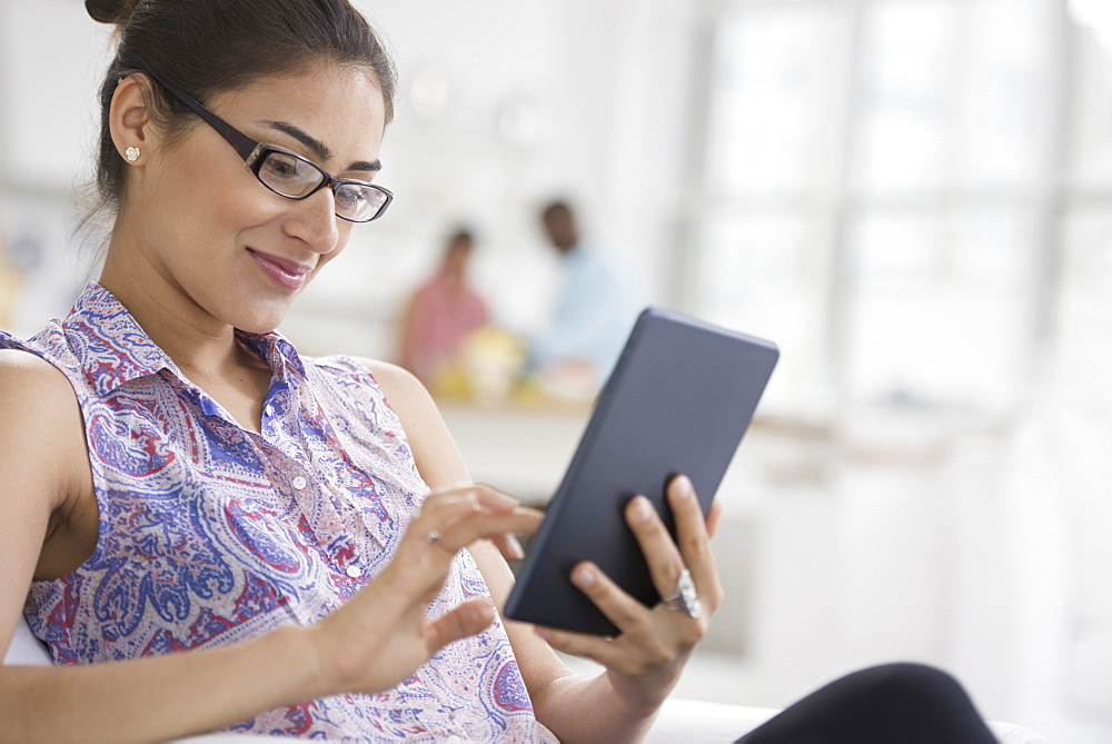 Professionals in the office. A light and airy place of work. A young woman seated using a digital tablet, New York City, USA
