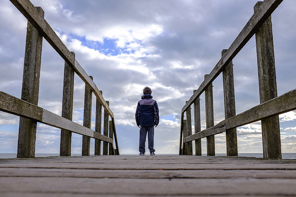 Rear view of a boy standing on a wooden jetty by the sea.