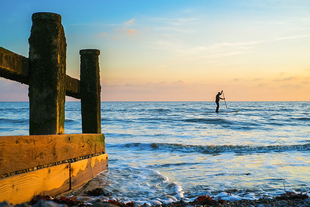 Man on a stand up paddle board on the ocean at sunset.