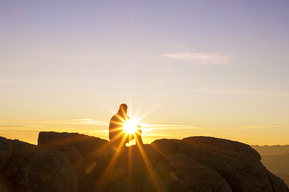 Man sitting on a rock on a summit at sunset.