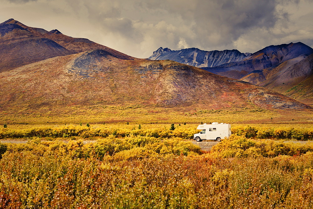 Dempster Highway Adventure, RV in autumn colour tundra landscape of Tombstone Territorial Park, Ogilvie Mountains, Yukon Territory, Canada.