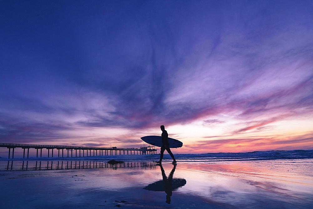 Surfer walking along a sandy beach at sunset, carrying a surfboard.