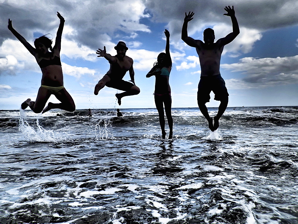 Silhouette of four people jumping into the ocean.