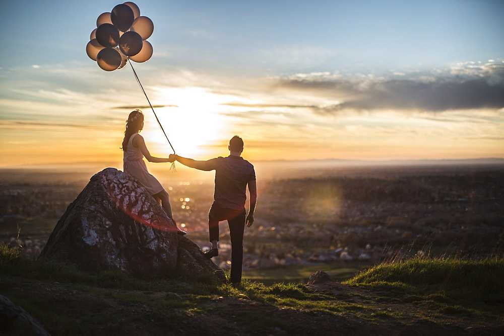 Couple sitting on a rock at sunset, holding hands and bunch of balloons.