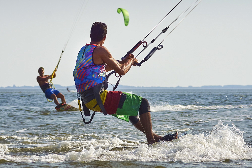 Two men kitesurfing.