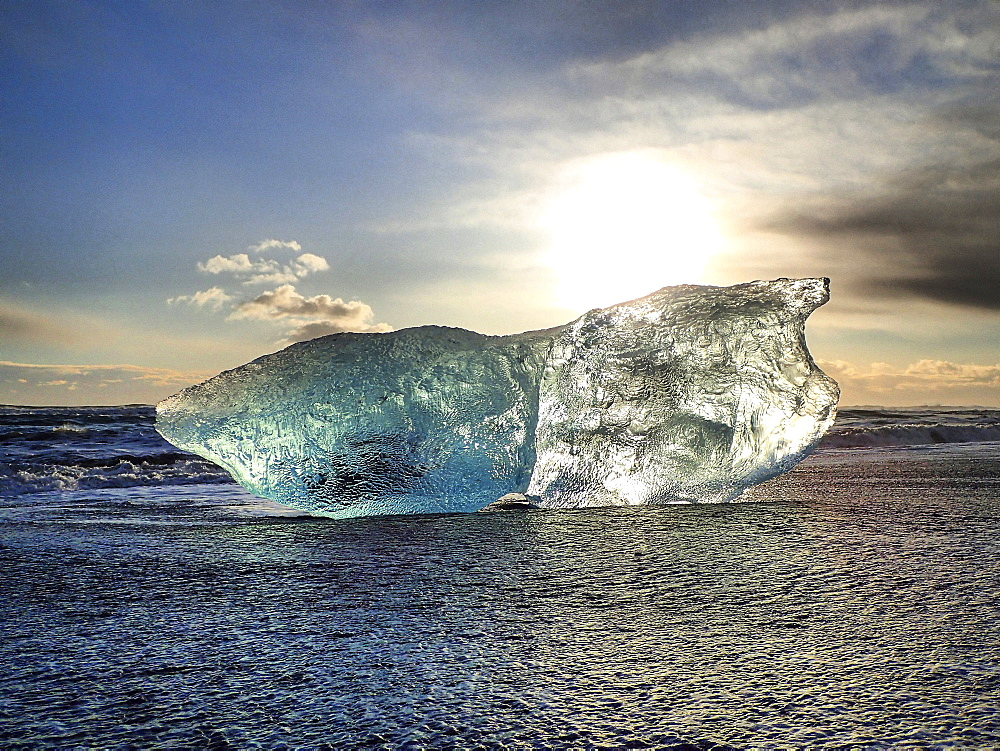 Glistening iceberg in the ocean at sunset.