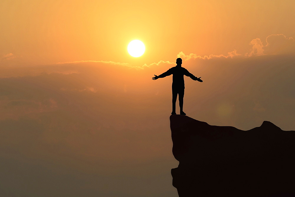 Man standing on a rock at sunset.