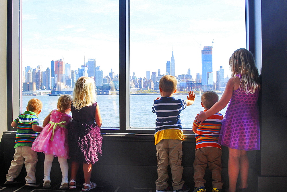 Group of children standing at a window, looking at the New York skyline.