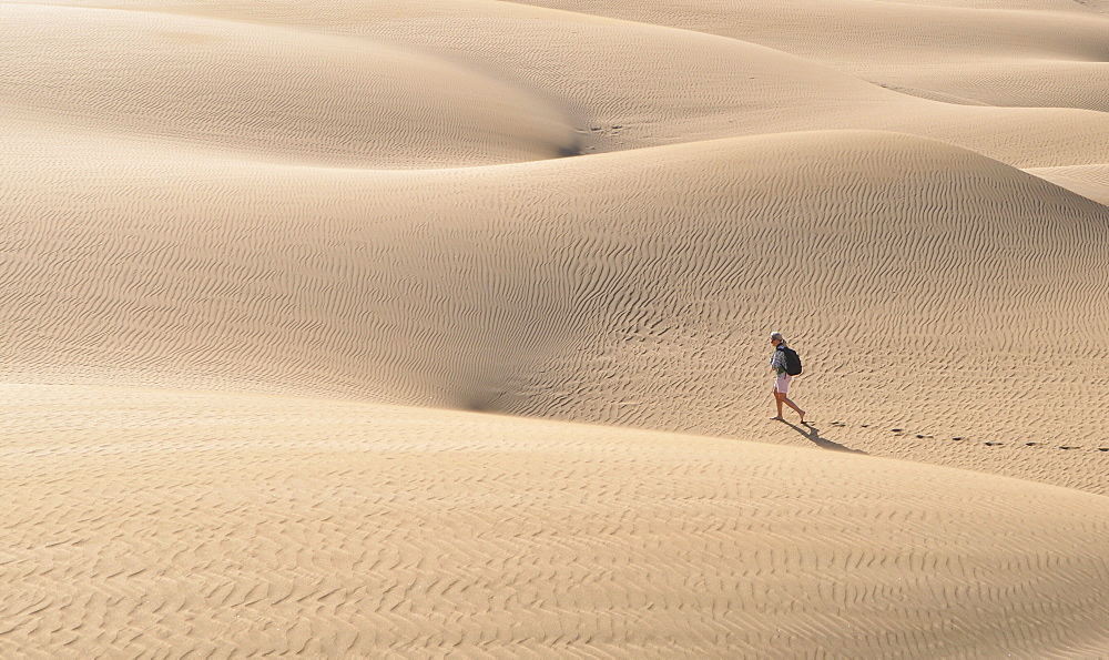 High angle view of a woman walking through sand dunes in the Arizona Desert.