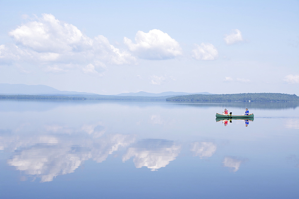 People in a canoe on a calm lake.