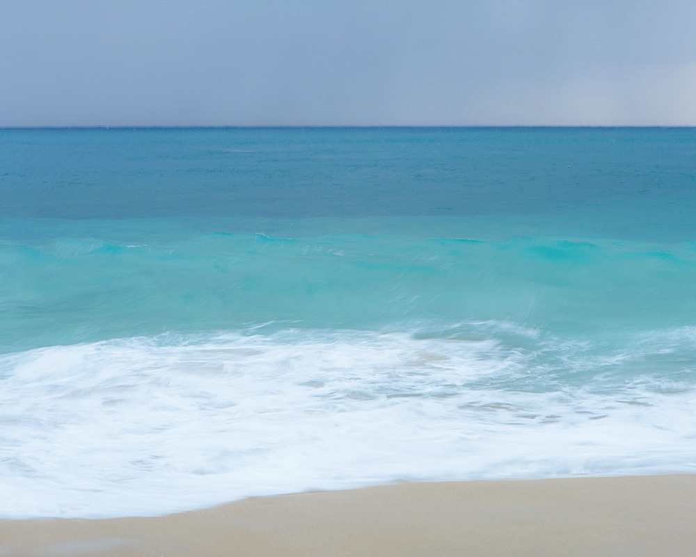 Turquoise sea, waves breaking on a sandy beach.