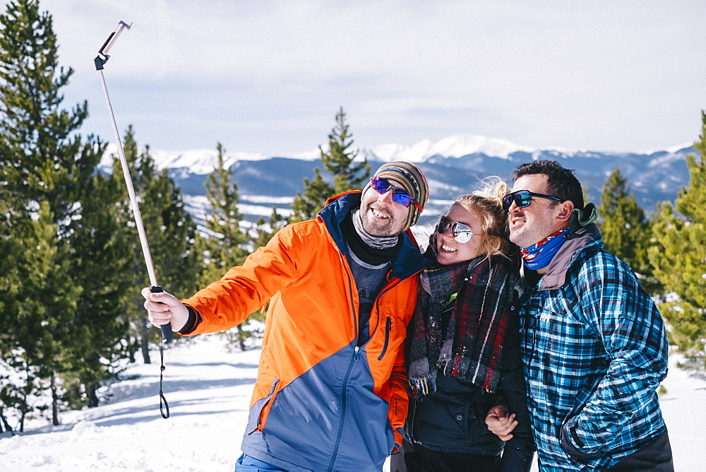 Three people, two men and a young woman in skiing gear posing for a selfie, one holding a selfie stick.
