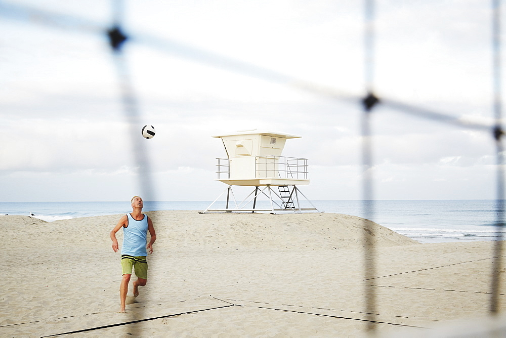 Mature man standing on a beach, playing beach volleyball, United States of America