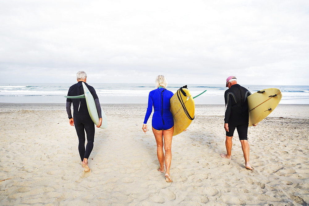 Senior woman and two senior men on a beach, wearing wetsuits and carrying surfboards, United States of America