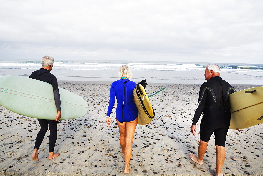Senior woman and two senior men on a beach, wearing wetsuits and carrying surfboards, United States of America - 1174-4200