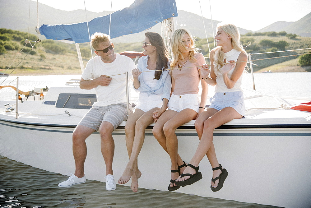 Man, woman and their two blond daughters on a sail boat.