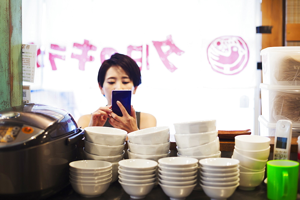 A woman using a smart phone at a noodle shop, Japan