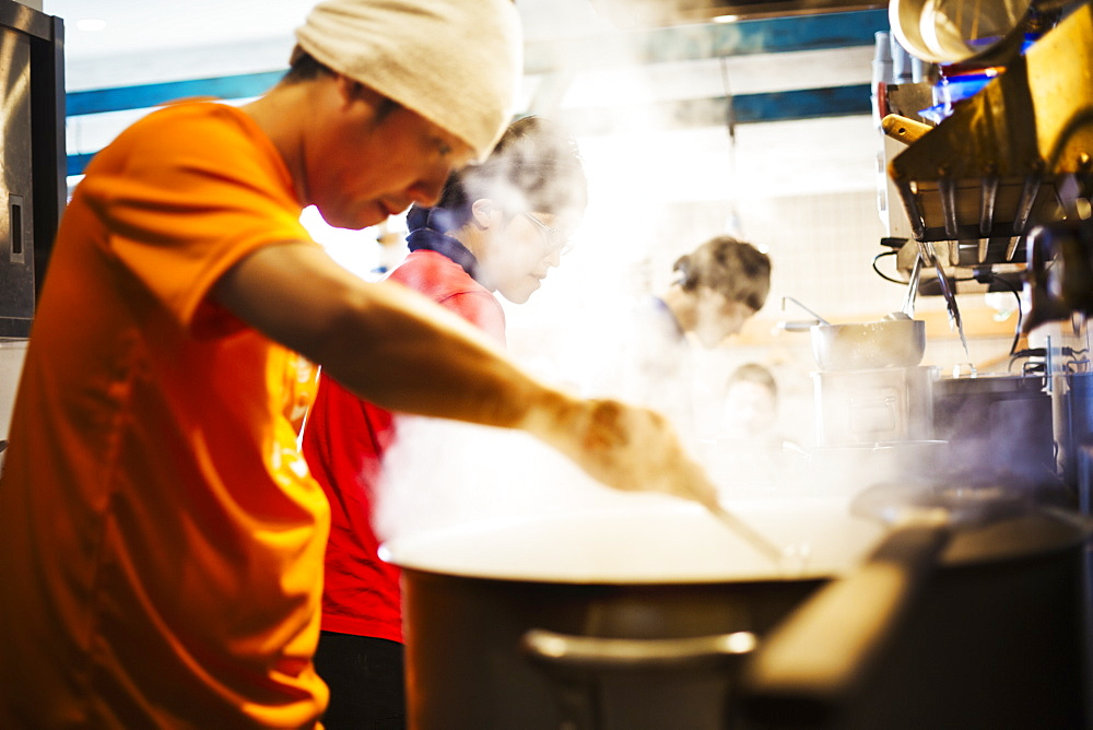 The ramen noodle shop. A chef stirring a huge pot of noodles cooking, Japan
