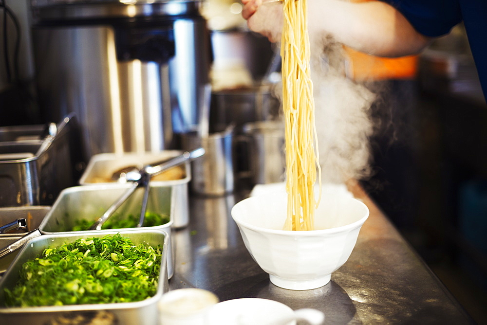 A ramen noodle shop kitchen. A chef preparing bowls of ramen noodles in broth, a speciality and fast food dish, Japan