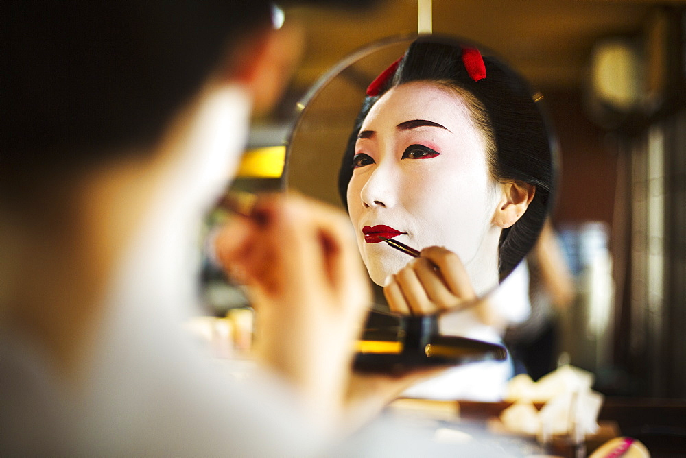 A modern geisha or maiko woman being prepared in traditional fashion, with white face makeup, Japan