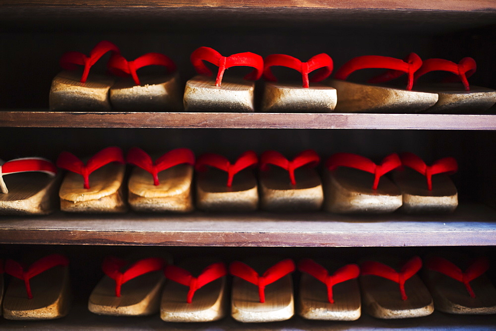 Rows of traditional wooden sandals with thick soles and red straps worn by geisha, okobo or geta, Japan