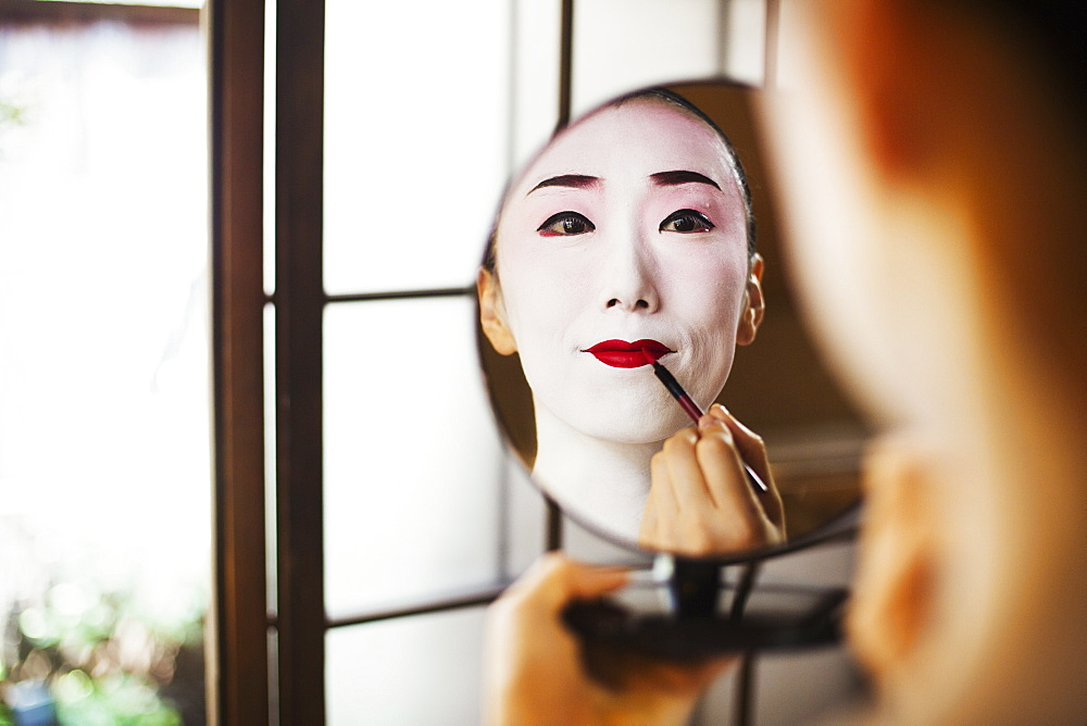 Geisha woman with traditional white face makeup applying bright red lipstick with a brush, using a mirror, Japan - 1174-4262